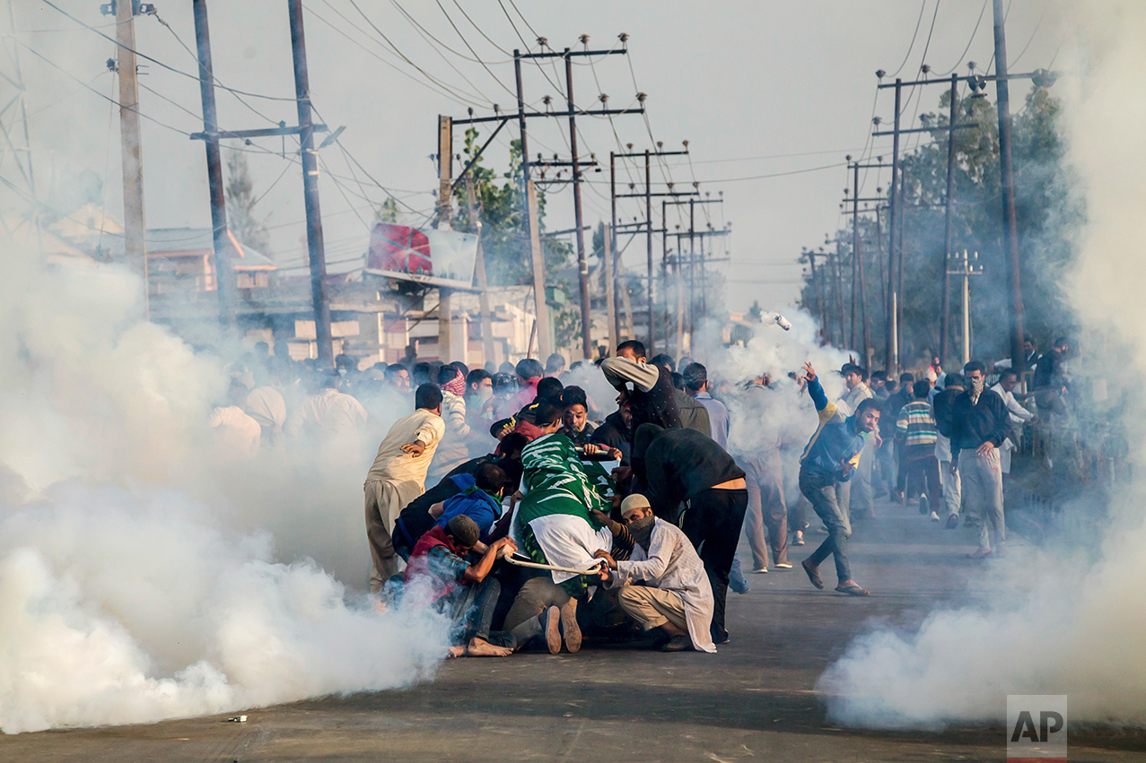 In this Saturday, Oct. 8, 2016 photo, relatives and neighbors of Junaid Ahmed, a 12-year-old boy huddle around his body as tear gas shells fired by Indian police men explode near them during his funeral procession in Srinagar, Indian-controlled Kashmir. Indian forces fired shotgun pellets and tear gas as thousands carried the body of a young boy killed overnight during an anti-India protest in the main city of Indian-controlled Kashmir. (AP Photo/Dar Yasin)