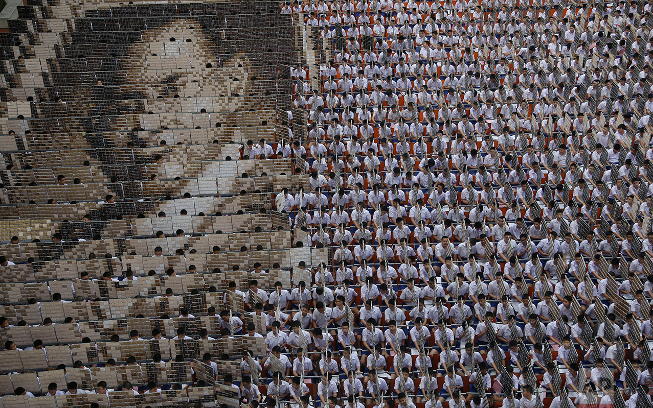 In this Oct. 28, 2016 photo, some 1,000 students practice flipping boards with photos to reveal a full-mosaic portrait of the late Thai King Bhumibol Adulyadej at Assumption College in Bangkok, Thailand. King Bhumibol died Oct. 13 after reigning for 70 years, plunging the country into grief and extended mourning. The official mourning period is one year. (AP Photo/Sakchai Lalit)