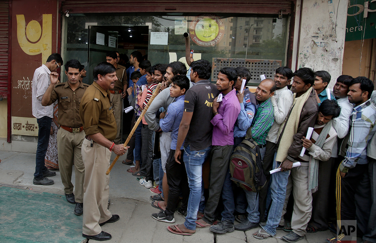 An Indian police officer warns people against breaking the queues as they wait to exchange or deposit discontinued currency notes, outside a bank on the outskirts of New Delhi, India, Tuesday, Nov. 15, 2016. (AP Photo/Altaf Qadri)