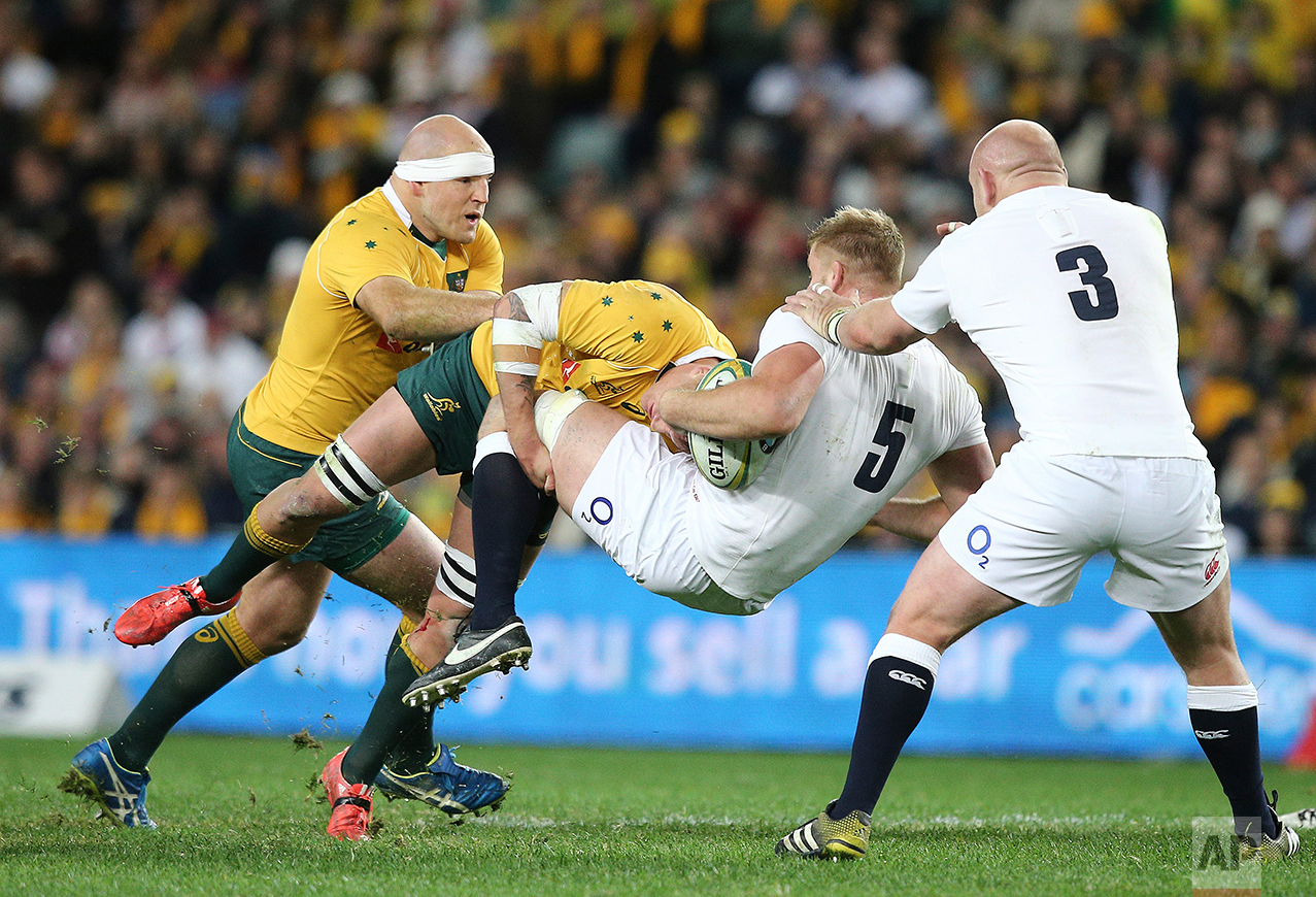 Australia's Sean McMahon, second left, and Stephen Moore, left, tackle England's George Kruis during their rugby test match in Sydney, Australia, Saturday, June 25, 2016. (AP Photo/Rob Griffith)