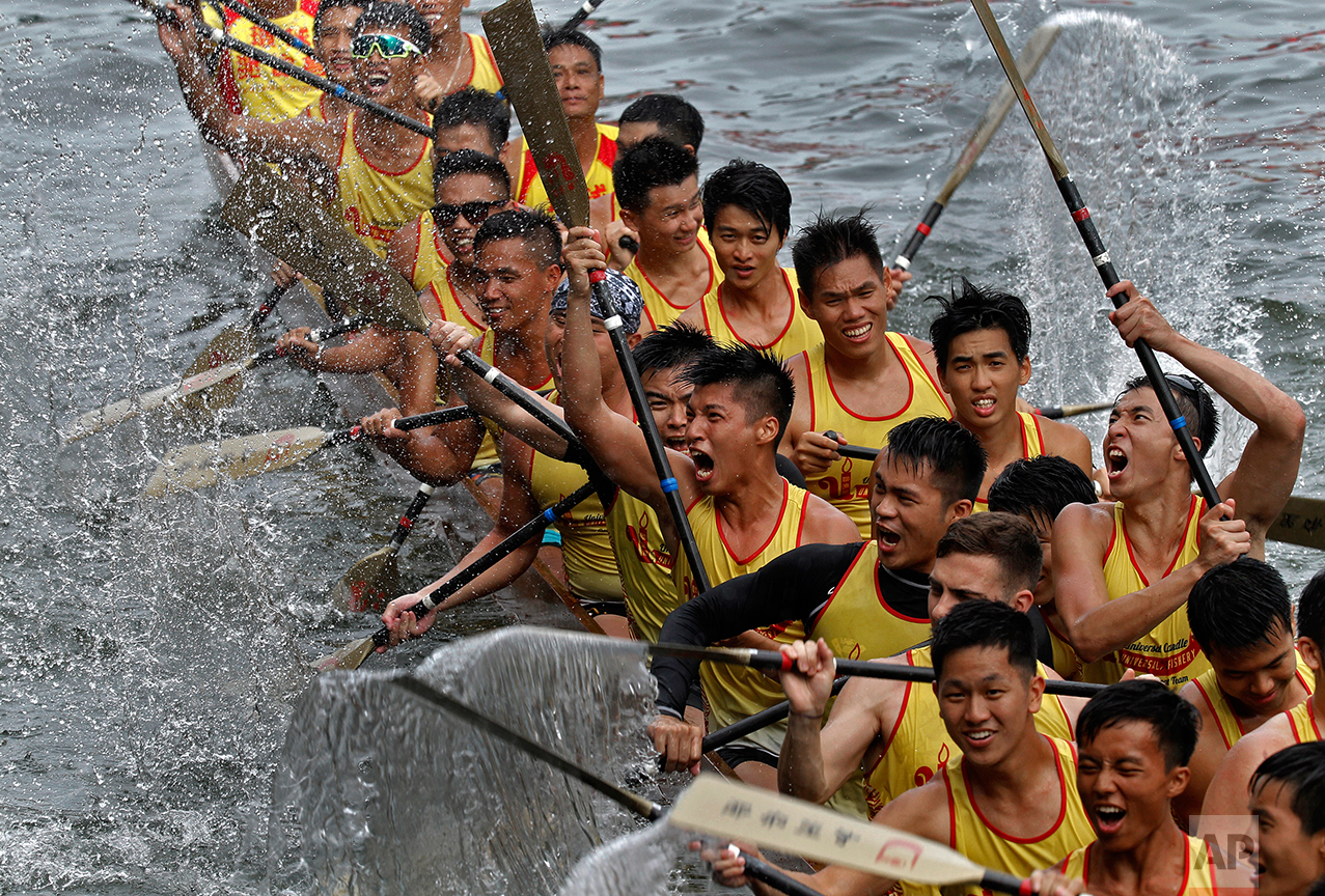 Participants celebrate after winning a dragon boat race in Hong Kong Thursday, June 9, 2016, as part of celebrations marking the Chinese Dragon Boat Festival, held throughout Hong Kong. (AP Photo/Vincent Yu)