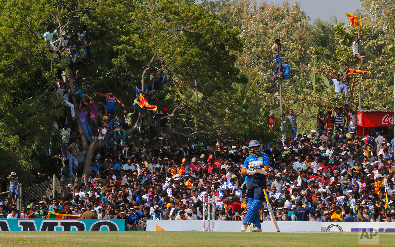 Sri Lankan cricket fans watch Tillakaratne Dilshan, foreground, from elevated positions during the third one day international cricket match between Australia and Sri Lanka in Dambulla, Sri Lanka, Sunday, Aug. 28, 2016. The match is the final one-day international for Sri Lankan opener Dilshan. (AP Photo/Eranga Jayawardena)
