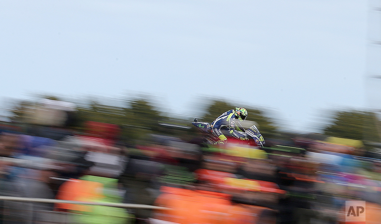 Yamaha MotoGP rider Valentino Rossi of Italy rides past fans going into turn 10 during the Australian Motorcycle Grand Prix at Phillip Island, Australia, Sunday, Oct. 23, 2016. (AP Photo/Rob Griffith)