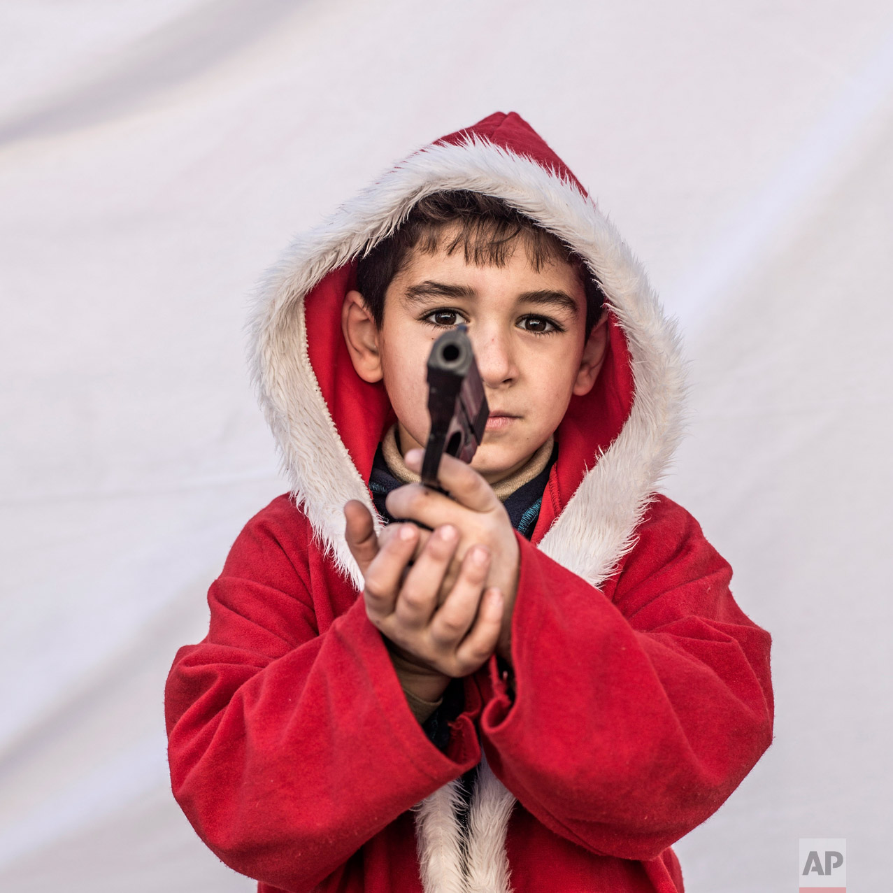 Kayaks, 7, poses for a picture holding a toy gun in a camp where Christians displaced by Islamic State militants are living, in Irbil, Iraq, Friday, Dec. 23, 2016. Iraq's Christians are marking the holiday in this camp for displaced people with a sense of worry and despair, unable to return to their towns they were forced to flee two years ago by the Islamic State group's onslaught. (AP Photo/Manu Brabo)