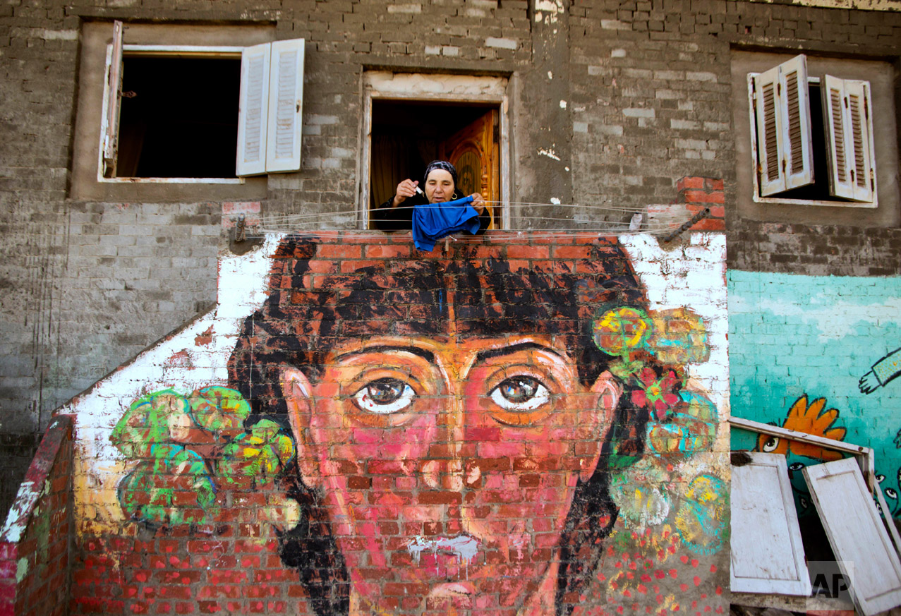 In this Thursday, Oct. 13, 2016 photo, an Egyptian woman hangs her laundry over a mural by Egyptian artist Omar El Fayoumi in Burullus, north of Cairo, Egypt. (AP Photo/Amr Nabil)