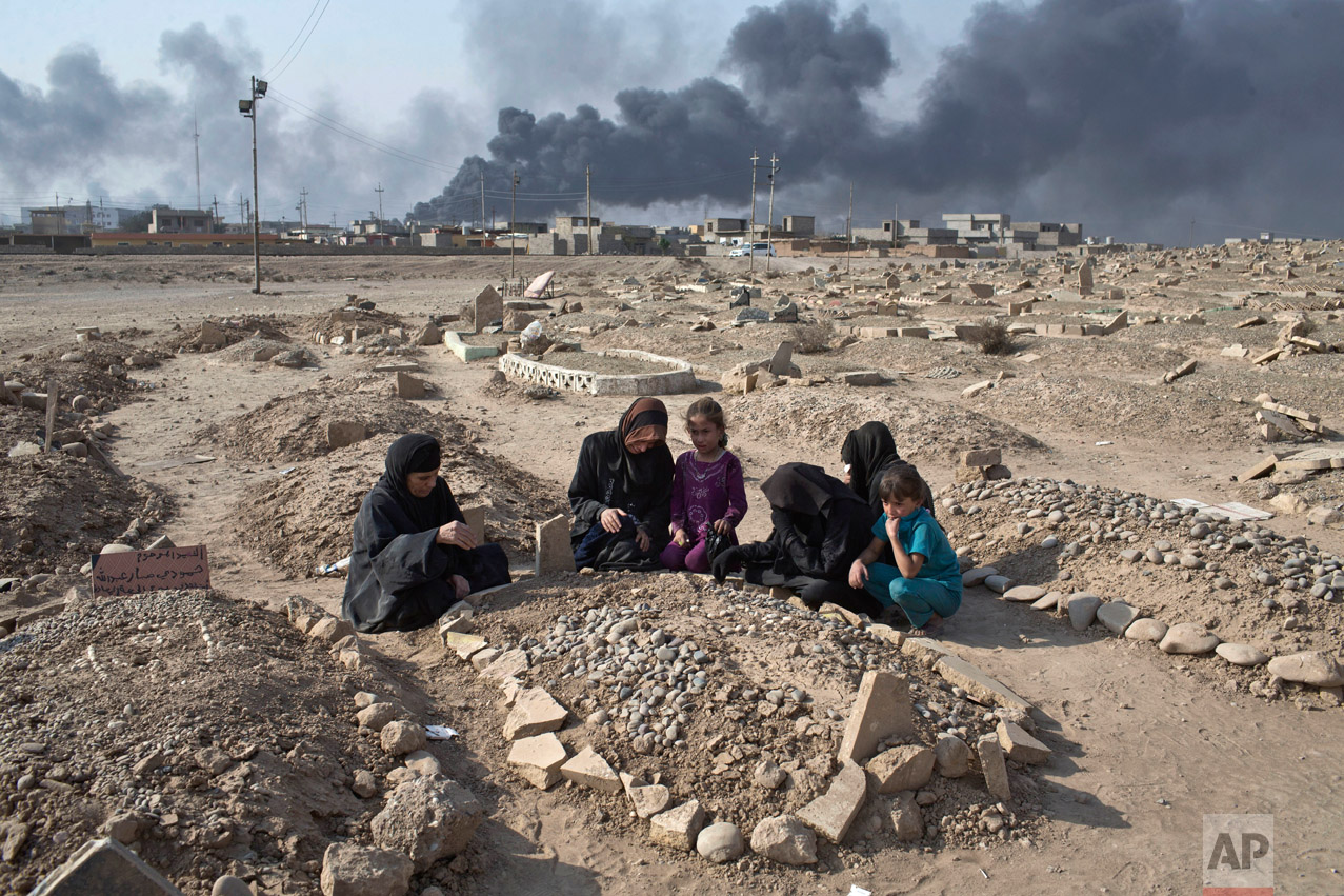 A family grieves over the grave of a family member at a graveyard damaged by Islamic State extremists in Qayara, some 31 miles, 50 km, south of Mosul, Iraq, Thursday, Oct. 27, 2016. (AP Photo/Marko Drobnjakovic)