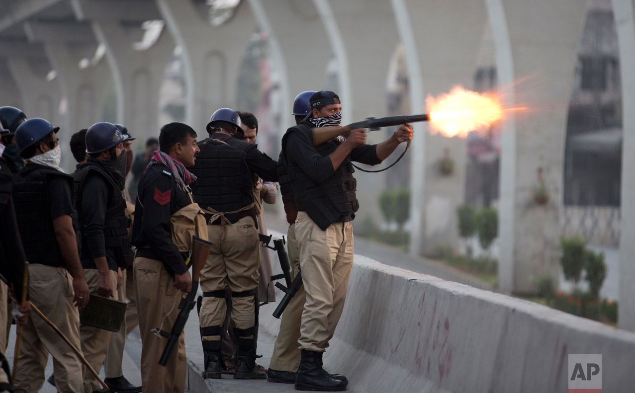 A Pakistani police officer fires tear gas shell to disperse crowd protesting against the government in Rawalpindi, Pakistan, Friday, Oct. 28, 2016. Pakistani police have charged with batons and fired tear gas at stone-throwing supporters of cricketer-turned-politician Imran Khan who are rallying in Islamabad in defiance of a government-imposed ban on demonstrations. (AP Photo/B.K. Bangash)