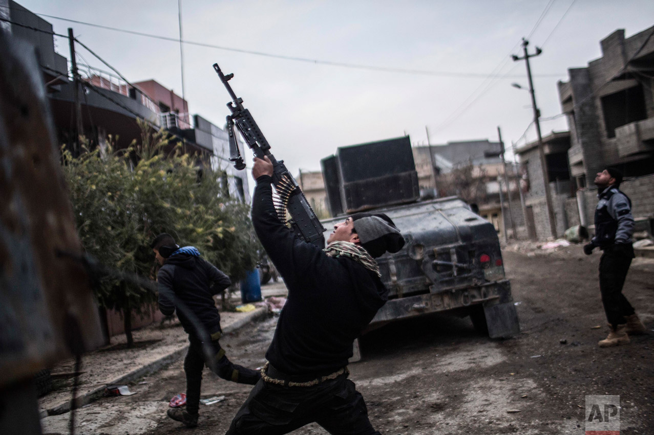 In this Sunday, Dec. 18, 2016 photo, a member of the Iraqi Special Forces shoots his machine gun against an Islamic State militant drone n the al-Barid district in Mosul, Iraq.(AP Photo/Manu Brabo)
