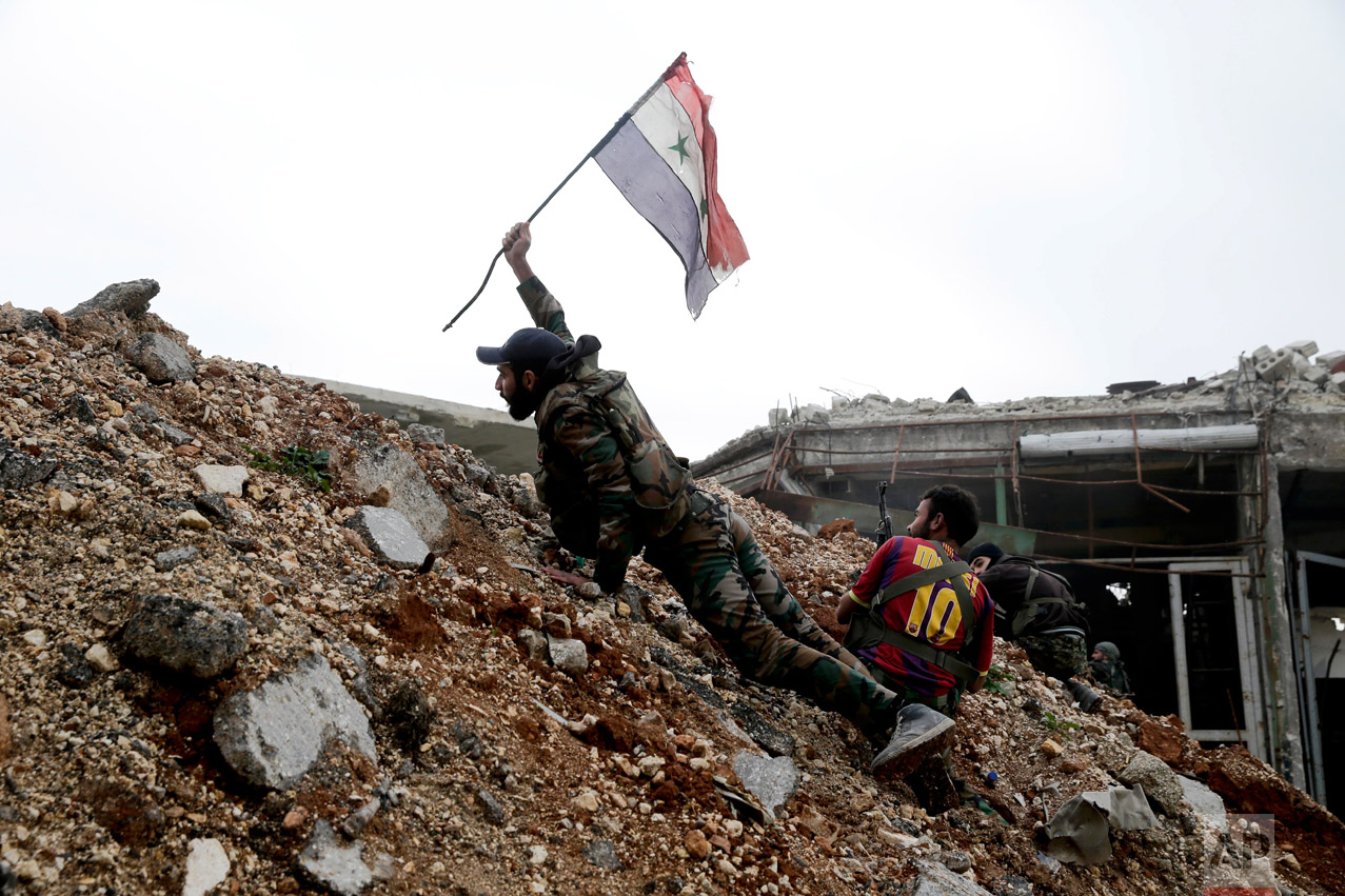 A Syrian army soldier places a Syrian national flag during a battle with rebel fighters at the Ramouseh front line, east of Aleppo, Syria, Monday, Dec. 5, 2016. (AP Photo/Hassan Ammar)