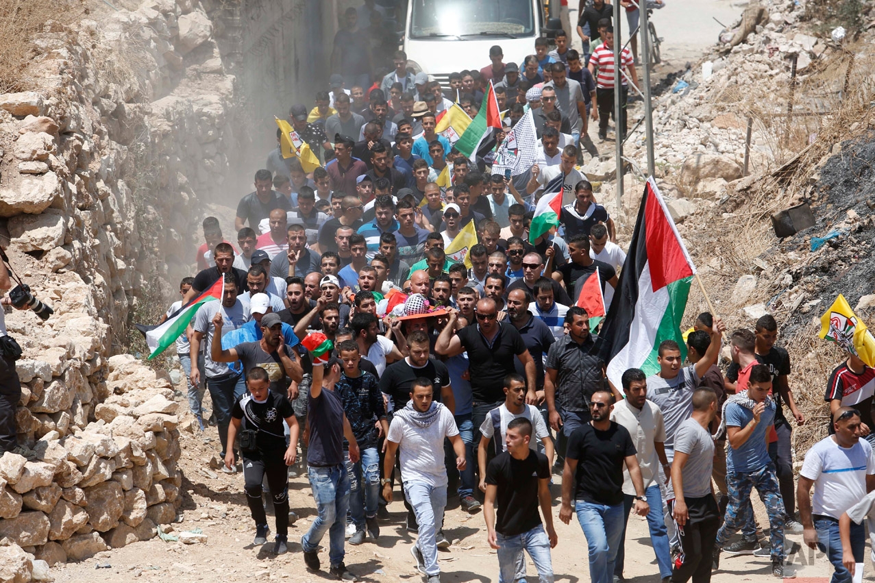 Mourners carry the body of Muhey al-Tabakhi, 12, during his funeral in the West Bank town of Al-Ram, near Jerusalem, Wednesday, July 20, 2016. A Palestinian hospital official says the boy was killed after clashes erupted between Israeli forces and protesters in the West Bank. Ramallah hospital director Ahmad Bitawi says the boy was killed by a bullet to the chest. Israeli police deny that live fire was used against protesters.(AP Photo/Nasser Shiyoukhi)