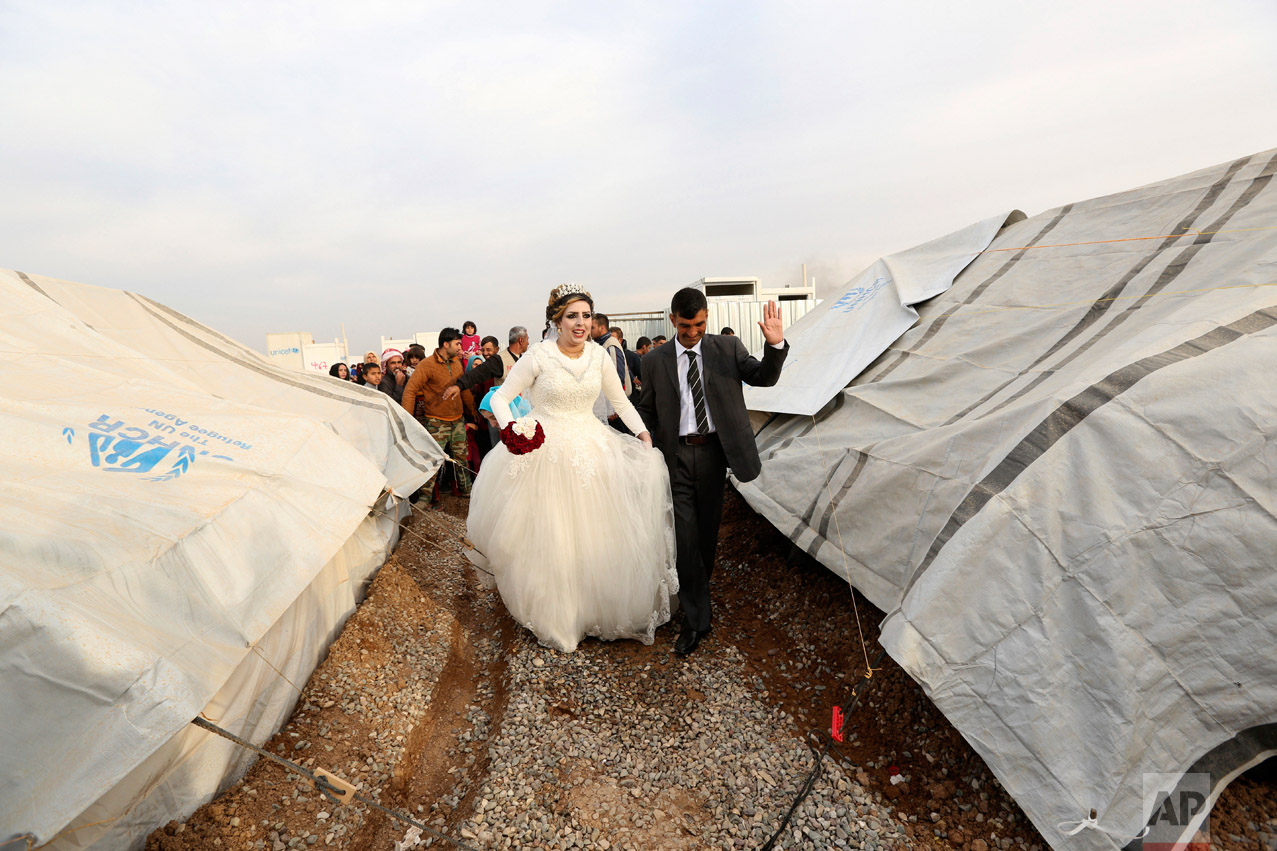 Iraqi internally displaced groom Jassim Mohammed walks with his bride, Amena Ali, during their wedding ceremony at a camp for internally displaced people, in Khazir, near Mosul, Iraq, Thursday, Dec. 8, 2016. (AP Photo/Hadi Mizban)