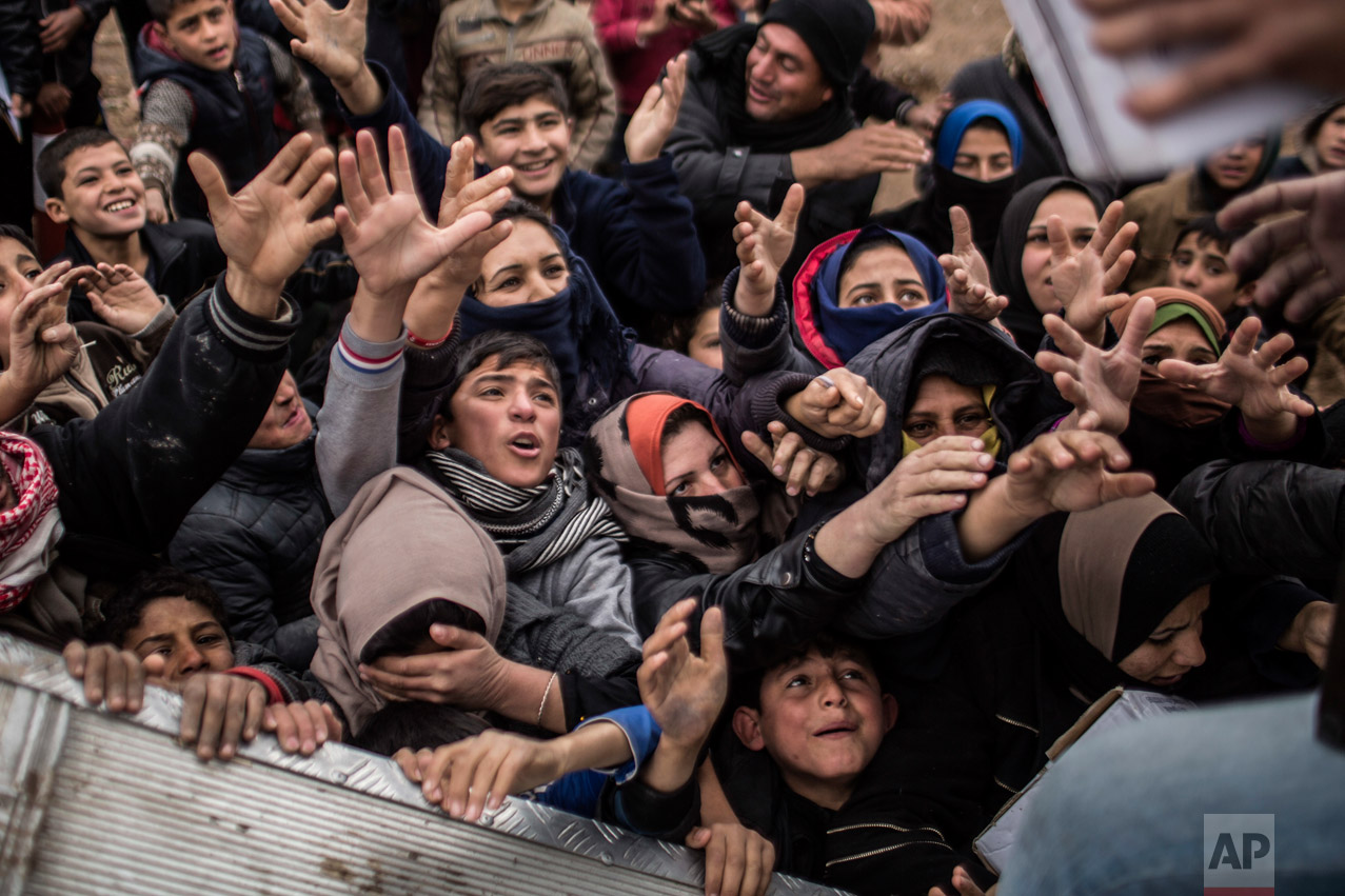 Iraqi displaced people plead for food during an aid distribution in Khazer camp for the displaced in Iraqi Kurdistan, Iraq, Saturday, Dec. 17, 2016. As Iraqi forces settle into a routine of slow, steadier progress inside Mosul, more civilians remain trapped living along front lines for longer. (AP Photo/Manu Brabo)