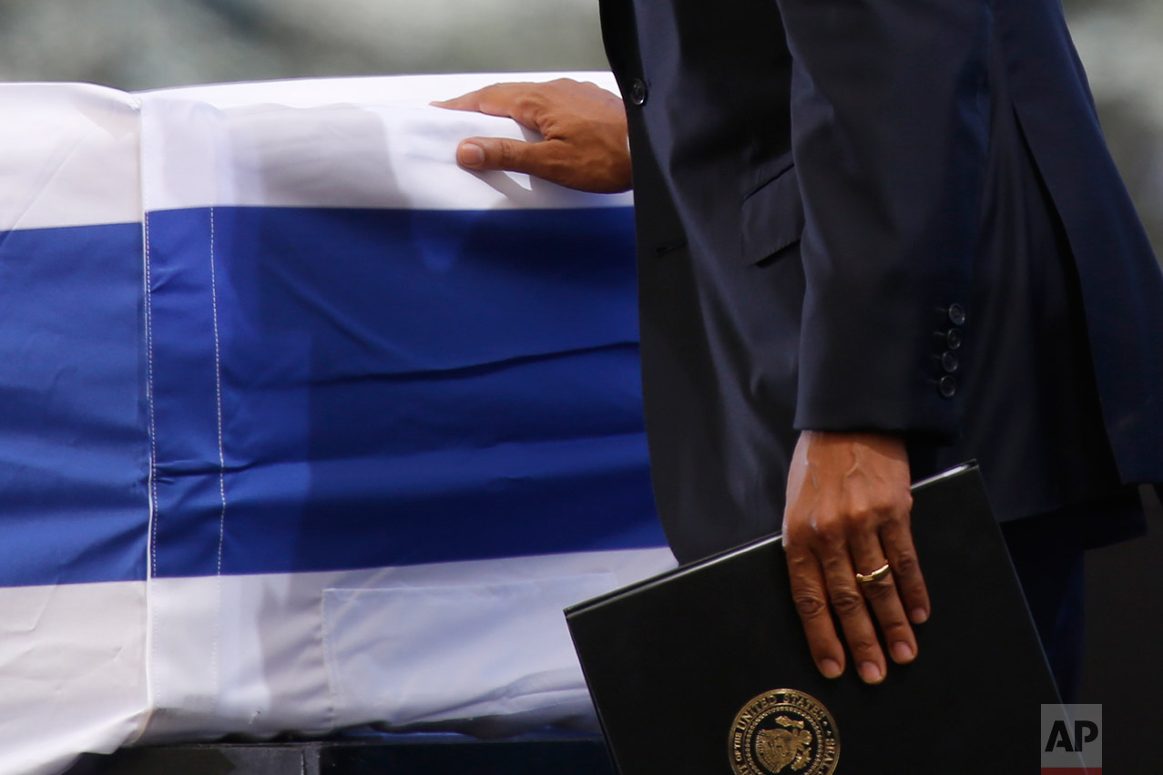 U.S. President Barack Obama touches the flag-draped coffin of former Israeli President Shimon Peres during his funeral at the Mount Herzel national cemetery in Jerusalem, Friday, Sept. 30, 2016. (AP Photo/Ariel Schalit)