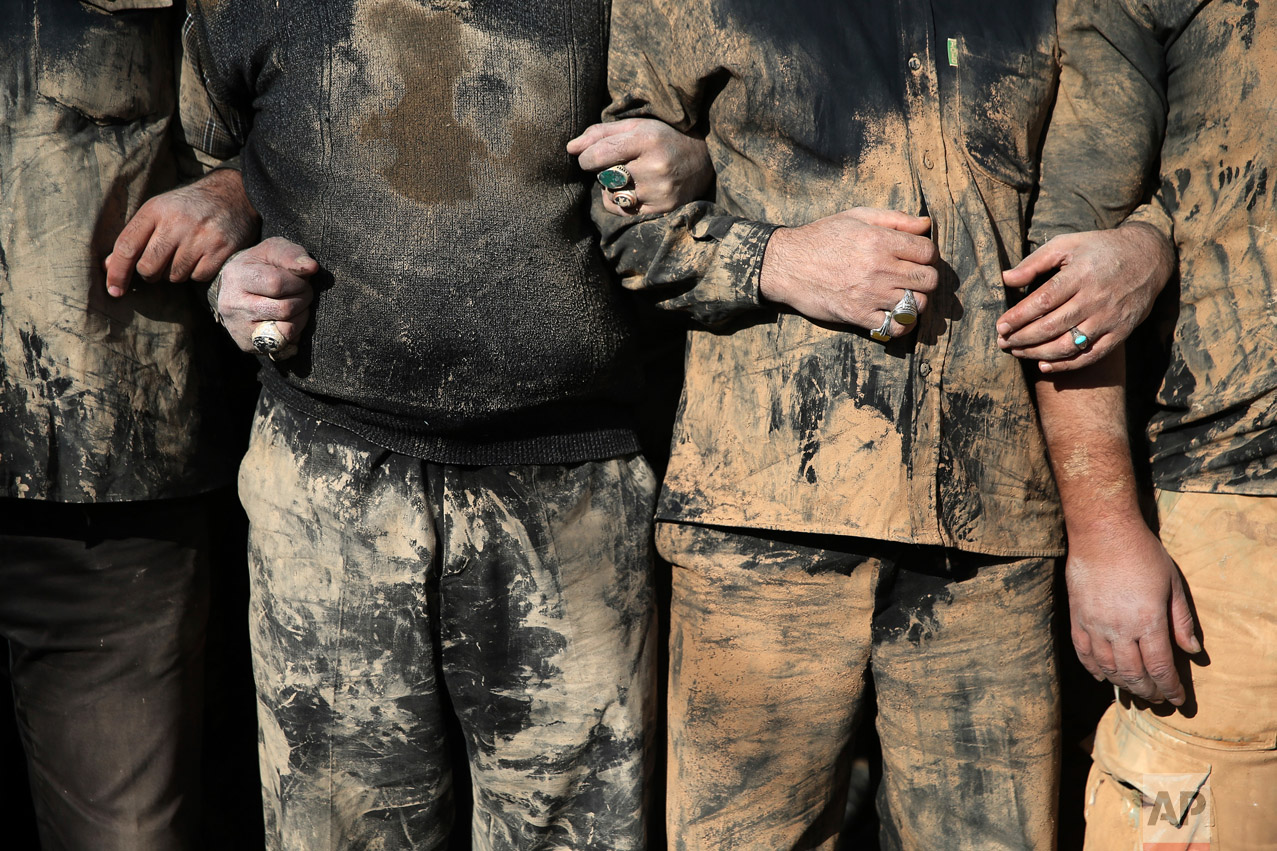 Iranian Shiite Muslims mourn after covering themselves with mud during Ashoura rituals, in Khorramabad, Iran, Wednesday, Oct.12, 2016. (AP Photo/Ebrahim Noroozi)