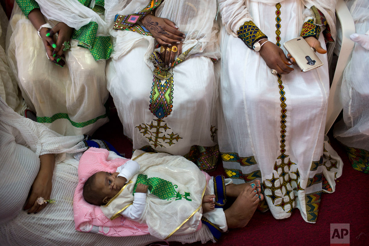 In this Saturday, April 23, 2016 photo, Eritrean Christian Orthodox migrant women attend a mass at a makeshift church in Tel Aviv, Israel. Hundreds of faithful gather each week in the makeshift churches. With its walls bedecked with Christian paraphernalia, it is an unlikely scene in the heart of the Jewish state, hidden in a non-descript building in hardscrabble south Tel Aviv. (AP Photo/Oded Balilty)
