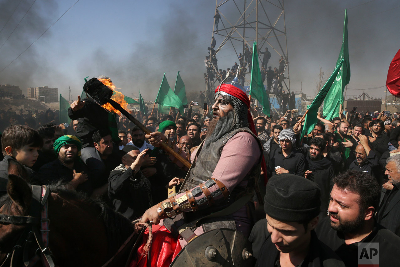 A Shiite re-enacts the events of Ashoura while Iranian and Iraqi Shiite Muslims mourn in a procession in southern Tehran, Iran, Wednesday, Oct. 12, 2016. Shiites mark Ashoura, the tenth day of the Muslim month of Muharram, to commemorate the martyrdom of Imam Hussein, a grandson of Prophet Muhammad and one of Shiite Islam's most beloved saints, during the 7th century Battle of Karbala in present-day Iraq. (AP Photo/Vahid Salemi)