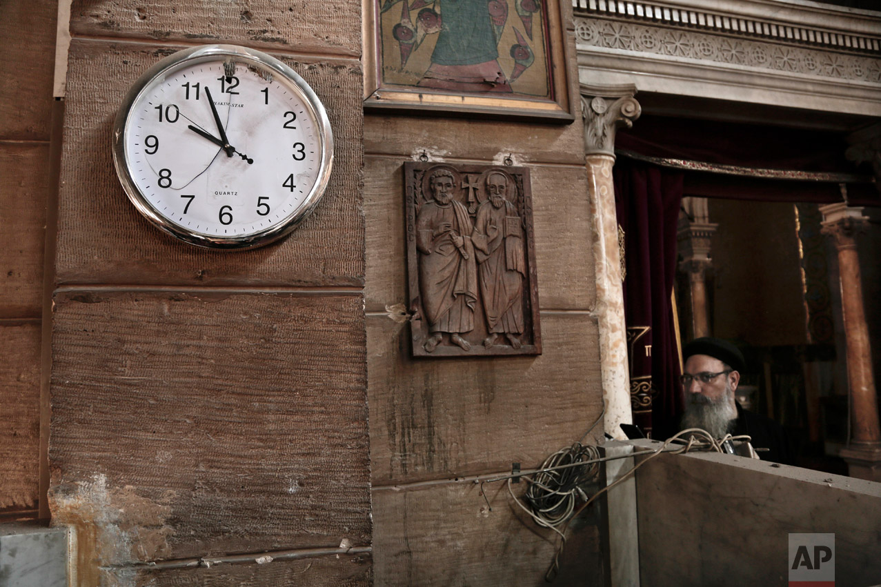 A damaged clock and Coptic clergyman at the scene inside the St. Mark Cathedral in central Cairo, following a bombing, Sunday, Dec. 11, 2016. The blast at Egypt's main Coptic Christian cathedral killed dozens of people and wounded many others, according to Egyptian state television, making it one of the deadliest attacks carried out against the religious minority in recent memory. (AP Photo/Nariman El-Mofty)