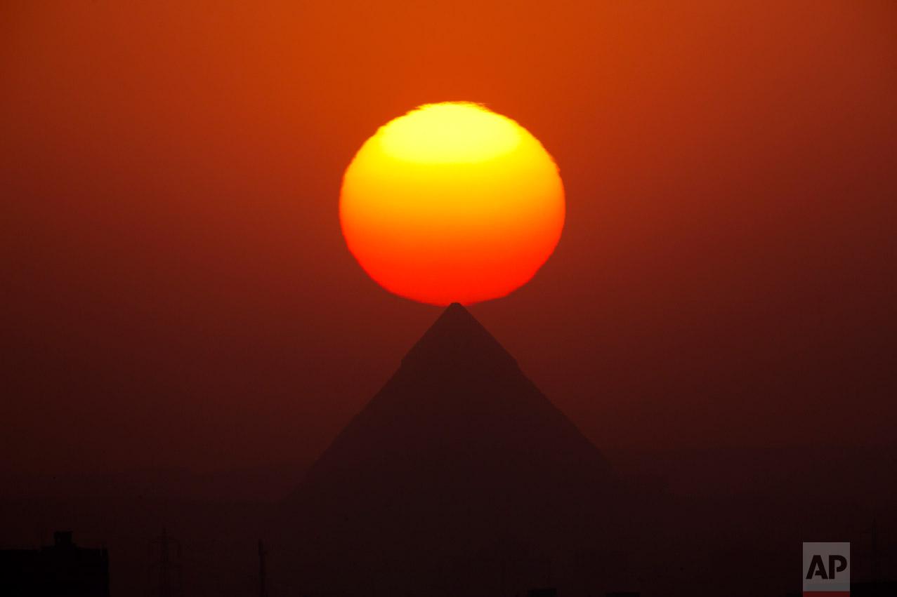The sun sets over the the Giza Pyramids, near Cairo, Egypt, Friday, Aug. 19, 2016. (AP Photo/Amr Nabil)
