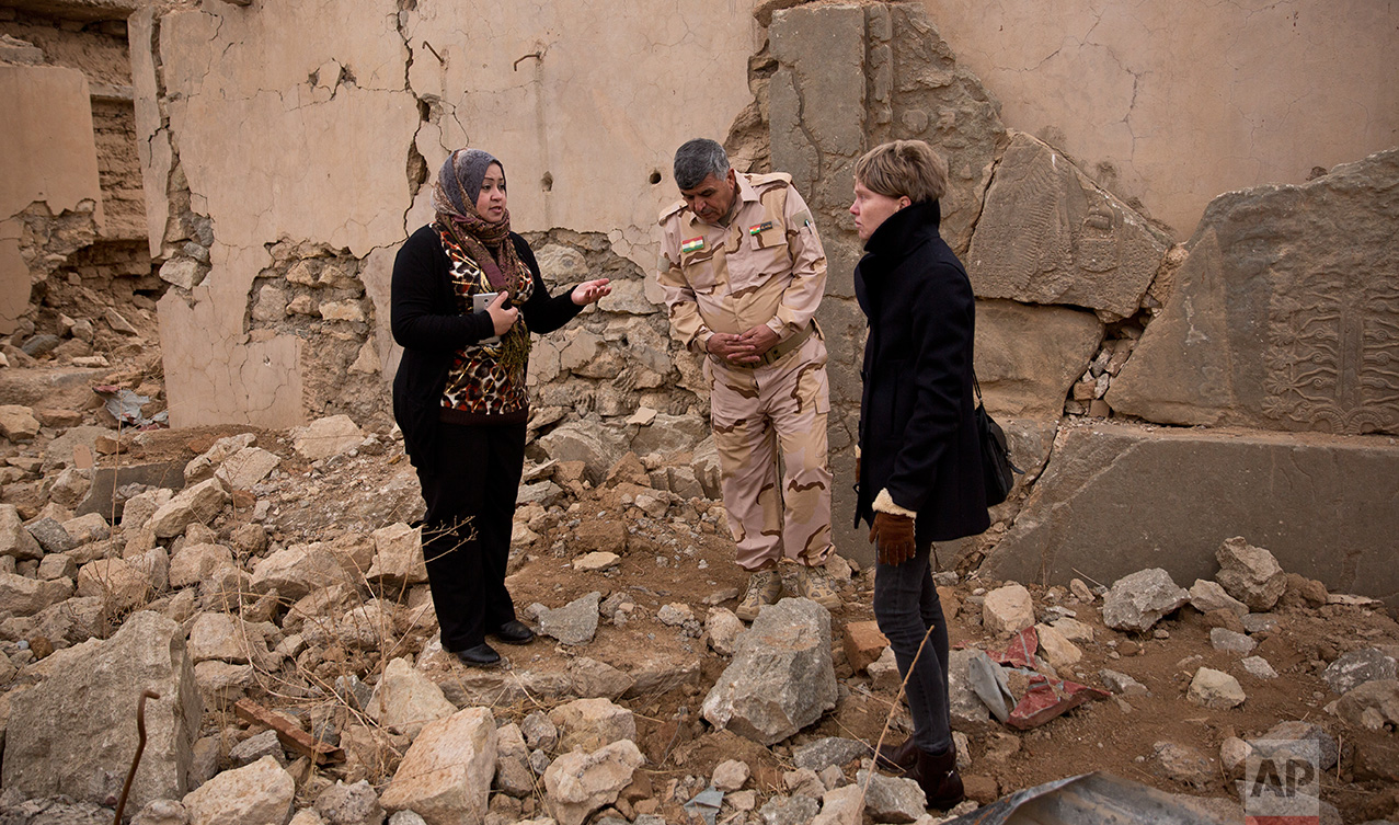 Iraq archaeologist Layla Salih, left, confers with UNESCO's representative in Iraq Louse Haxthausen, right, at the ancient site of Nimrud, Iraq, in this Wednesday, Dec. 14, 2016 photo. Days after Iraqi forces drove the Islamic State group from Nimrud in November, Salih arrived to survey the damage they wreaked on the nearly 3,000-year-old site. She confirmed that, as international forces closed in this fall, IS bulldozed a 140-foot tall ziggurat, or step pyramid, that archaeologists had never had to chance to explore. (AP Photo/Maya Alleruzzo)