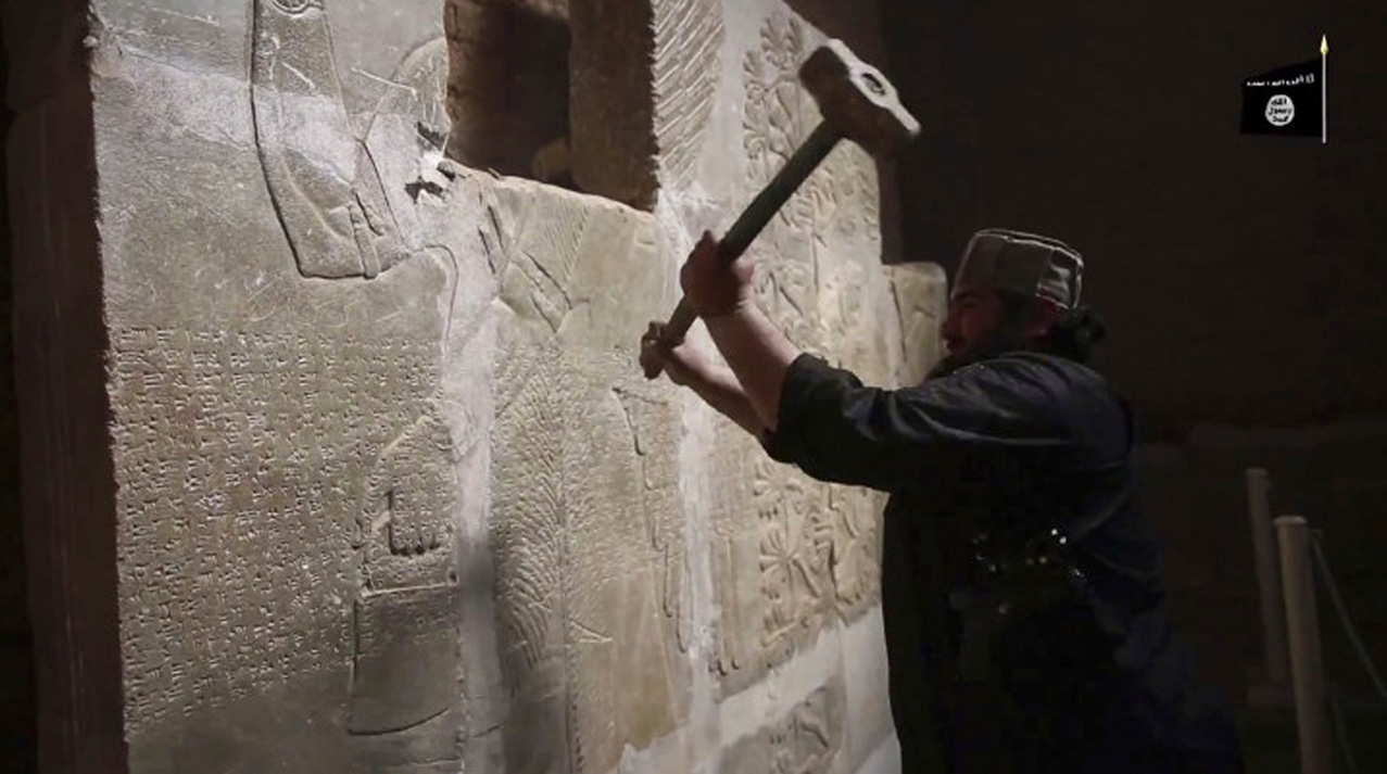 This image made from video posted online by Islamic State militants in April 2015 shows a militant taking a sledgehammer to a stone carving at the ancient site of Nimrud near Mosul, Iraq. Militants blew up and hacked apart much of the nearly 3,000-year-old city's remains, destroying one of the Mideast's most important archaeological sites. Nearly a month after the extremists were driven out, the site is still in danger, with the wreckage unprotected and vulnerable to being stolen. (Militant video via AP)