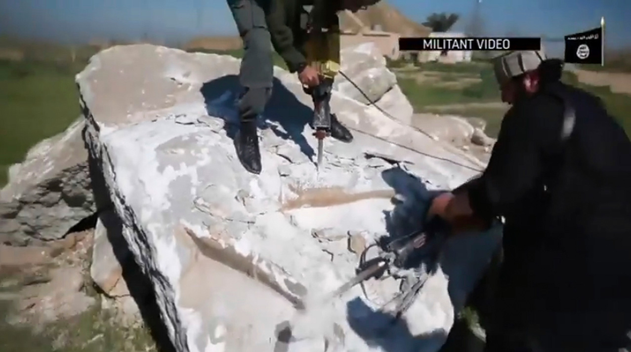 """This image made from video posted online by Islamic State group militants in April 2015 shows militants using heavy tools to destroy a large stone figure of a lamasssu, an Assyrian winged bull deity at the ancient site of Nimrud near Mosul, Iraq. The militants boasted of their destruction of one of the Middle East's most important archaeological sites in high-definition video propaganda, touting their campaign to purge their """"caliphate"""" of anything they considered as heretical or pagan. (Militant video via AP)"""