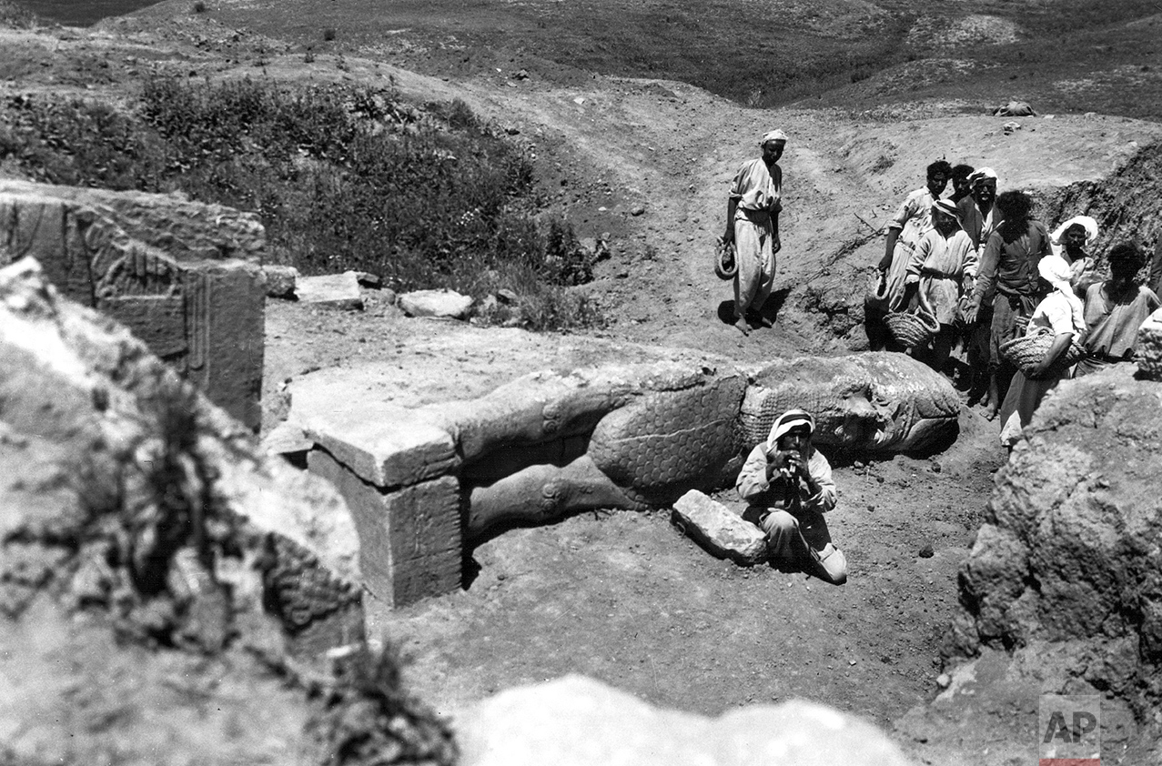 """People gather around the partially-unearthed statue of a lamassu, a great winged bull protective deity, in this undated photo taken by British mystery writer Agatha Christie at the ancient site of Nimrud in northern Iraq. The lamassus at the palace gates were among the works destroyed by IS militants in 2015. Christie's grandson, Matthew Prichard, says she would be heartbroken by the destruction, saying if she and her husband Max Malloran, were alive to see it, """"they would not have recognized the places where they had been and lived and worked."""" (Agatha Christie via AP)"""