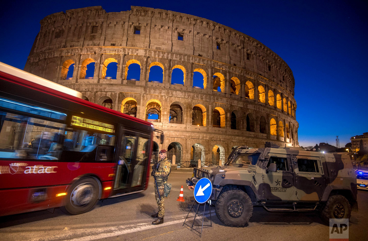 A bus drives past a soldier patrolling the ancient Colosseum area in Rome on Wednesday, Dec. 28, 2016. Italy has been strengthening security measures for areas where crowds are expected. (Claudio Peri/ANSA via AP)