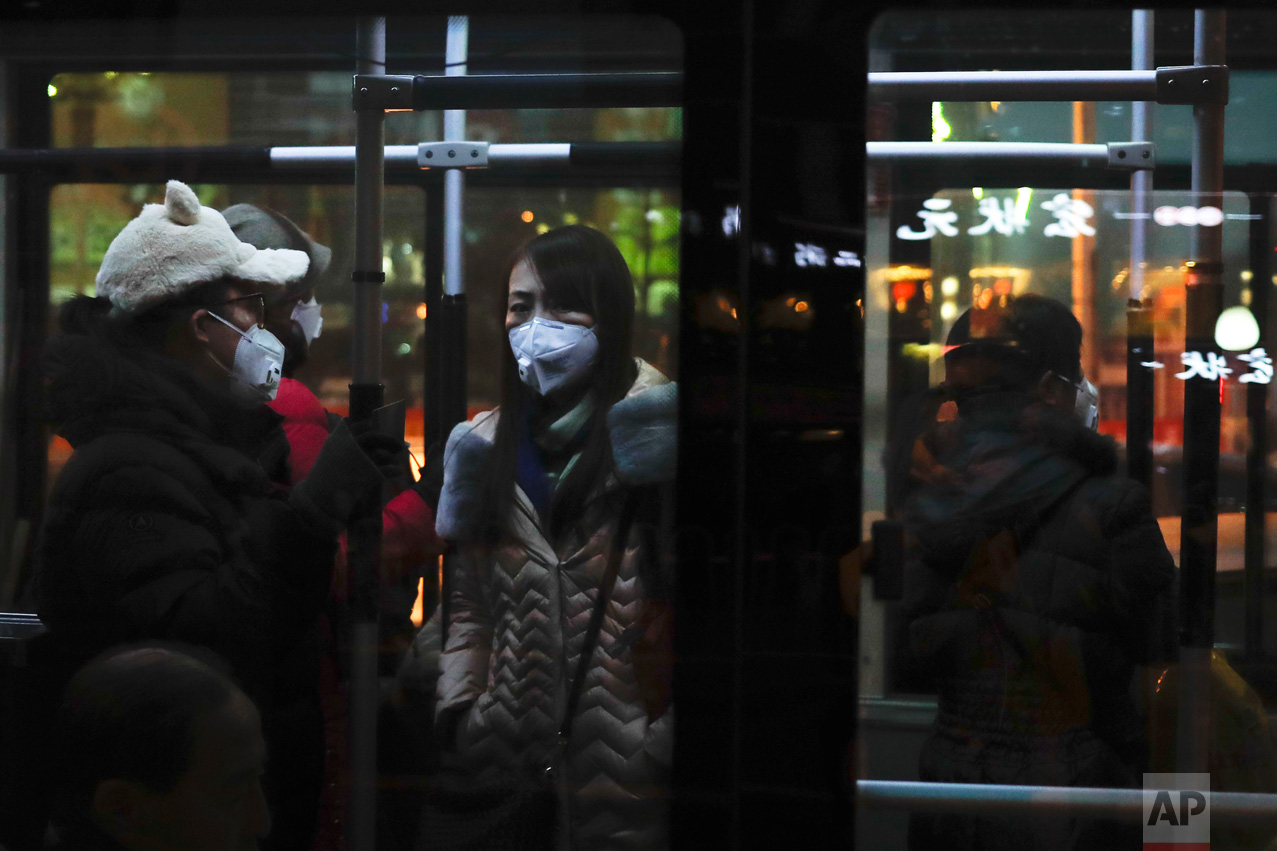 Passengers wearing masks stand inside a bus in Beijing as the Chinese capital is blanketed by smog on Friday, Dec. 30, 2016. China has long had some of the worst air in the world, blamed on its reliance on coal and a surplus of older, less efficient cars. It has set pollution reduction goals, but also has plans to increase coal mining capacity and eased caps on production when faced with rising energy prices. (AP Photo/Andy Wong)