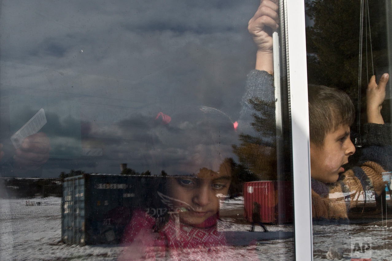 Syrian refugee Fatima Slu, 5, and her brother, Banken, 6, whose family fled from Aleppo, look out from their family's shelter during a snowfall at the Ritsona, Greece refugee camp about 86 kilometers (53 miles) north of Athens, on Friday, Dec. 30, 2016. Over 62,000 refugees and migrants are stranded in Greece after a series of Balkan border closures and a European Union deal with Turkey to stop migrant flows. (AP Photo/Muhammed Muheisen)