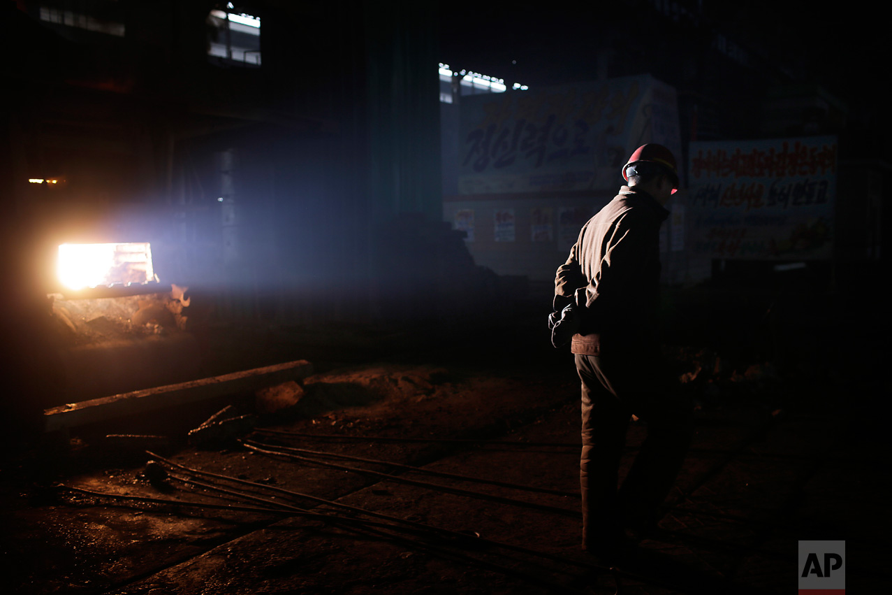 In this Saturday, Jan. 7, 2017 photo, a North Korean worker is illuminated by a shaft of light from a furnace at the Chollima Steel Complex in Nampo, North Korea. North Korean officials and factory managers are scrambling to answer a call from leader Kim Jong Un for an all-out, nationwide effort to build up the country's economy in 2017. The sprawling Chollima complex south of Pyongyang, the capital, is a focal point of North Korea's effort to expand the economy and lift the nation's standard of living. One of seven North Korean steel works, Chollima has more than 8,000 workers and is among the North's showcase enterprises. (AP Photo/Wong Maye-E)