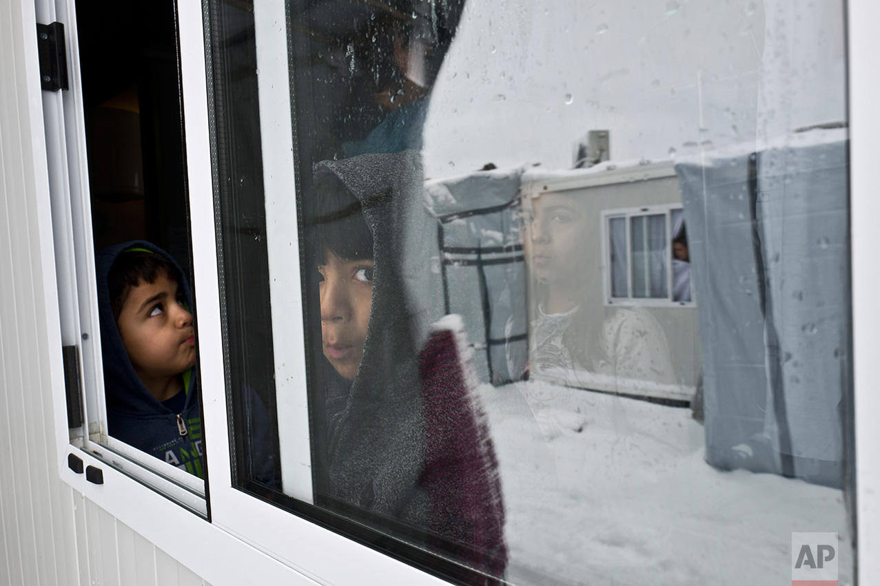 Syrian refugee children look out their shelter during snowfall at the refugee camp of Ritsona about 86 kilometers (53 miles) north of Athens, Tuesday, Jan. 10, 2017.  (AP Photo/Muhammed Muheisen)