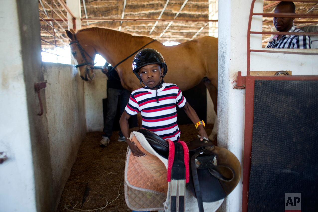 In this Jan. 7, 2017 photo, Judeley Hans Debel, who walks on a prosthetic right leg, carries his saddle away after riding Tic Tac at the Chateaublond Equestrian Center in Petion-Ville, Haiti. After riding, Judeley gives Tic Tac a bath, and is also learning how to help hoist saddles onto the animals and prepare them for rides. (AP Photo/Dieu Nalio Chery)
