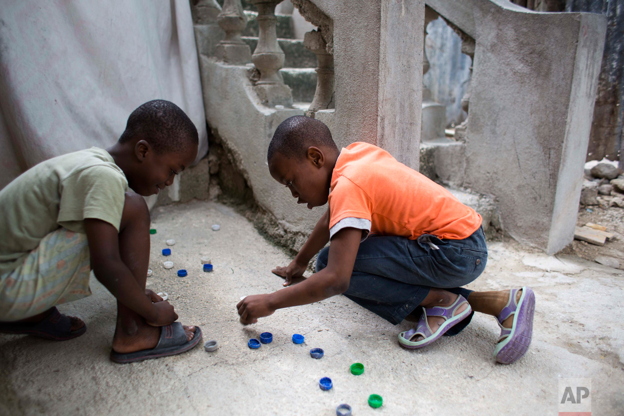 In this Jan. 8, 2017 photo, Judeley Hans Debel, right, who's right leg is a prosthesis, plays bottle cap soccer with a neighbor at his home in Petion-Ville, Haiti. Just 2 ½ years old at the time, Judeley's tiny body was pinned under earthquake rubble at his shattered concrete home in 2010. His mother dug him out and rushed him to a hospital where his leg was amputated. (AP Photo/Dieu Nalio Chery)