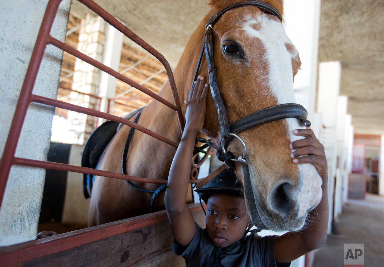 """In this Jan. 11, 2017 photo, Judeley Hans Debel, whose right leg is a prosthesis, caresses Tic Tac after riding her at the Chateaublond Equestrian Center in Petion-Ville, Haiti. """"You're the best horse, you're the best horse,"""" the 9-year-old said soothingly to the tan polo pony when he arrived at her stable. (AP Photo/Dieu Nalio Chery)"""