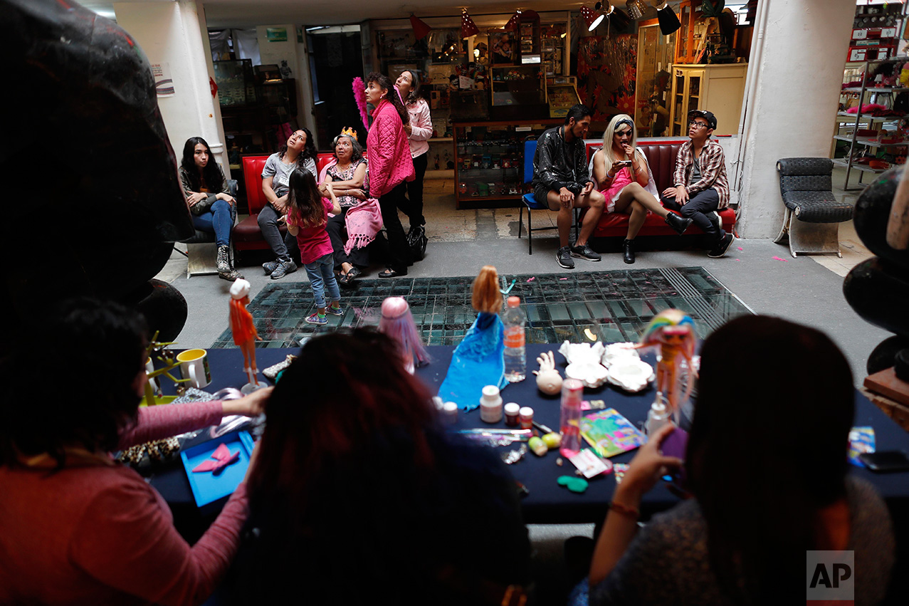 In this Jan. 6, 2017 photo, visitors watch as a doll making workshop takes place during a Barbie Doll temporary exhibit at the Mexico Antique Toy Museum in Mexico City. Several Barbie doll collectors teamed up to display their dolls in this museum. (AP Photo/Dario Lopez-Mills)
