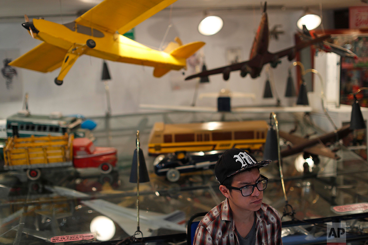 """In this Jan. 6, 2017 photo, a visitor stands among model airplanes and trucks at the Mexico Antique Toy Museum in Mexico City.Tucked in the middle of the capital's historic but seedy Doctores neighborhood, the museum is stuffed with Legos, superhero action figures, robots, model airplanes, trains and """"lucha libre"""" wrestling masks as well as old traditional Mexican toys. (AP Photo/Dario Lopez-Mills)"""
