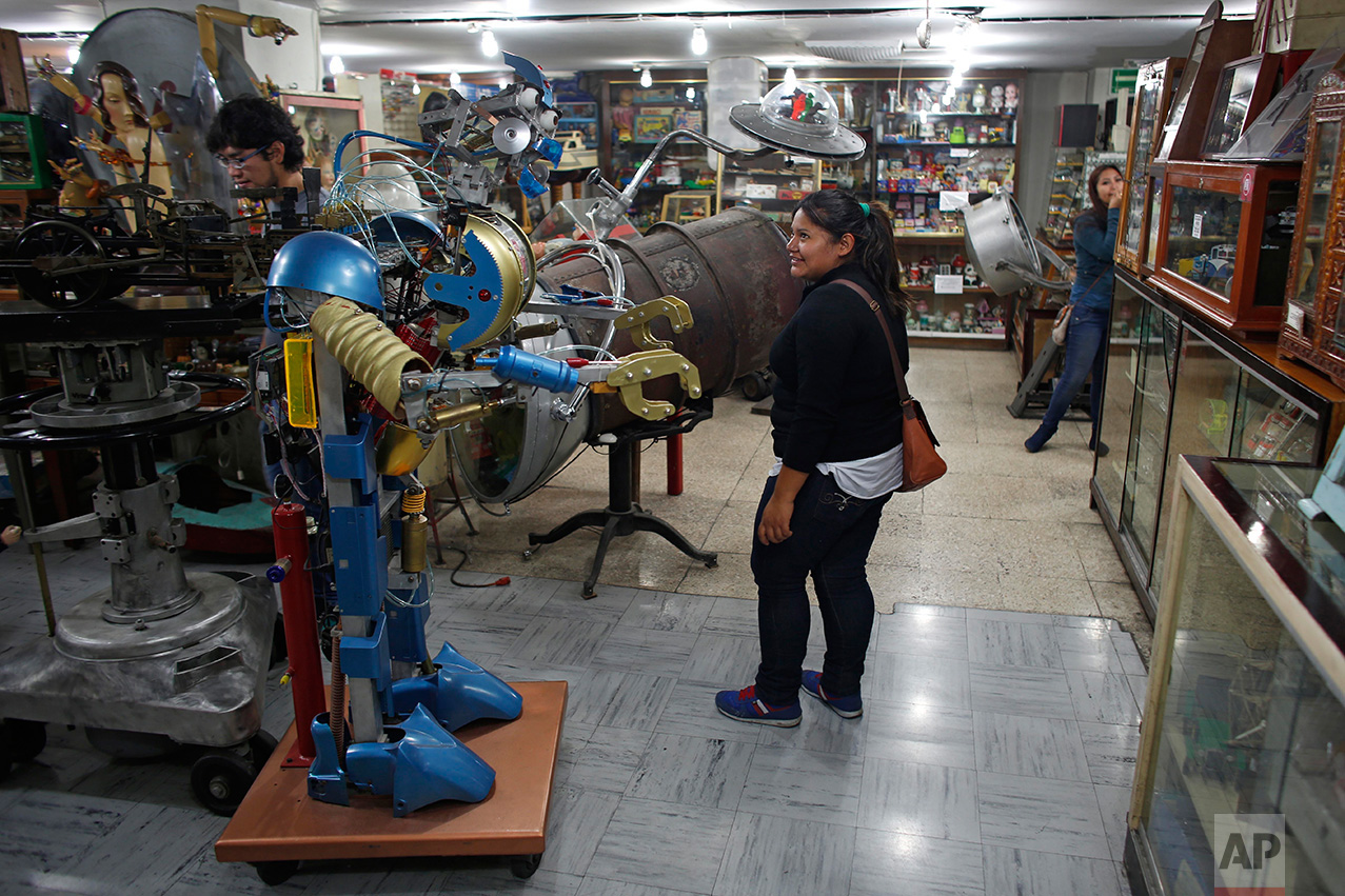 In this Jan. 11, 2017 photo, visitors look at items displayed at the Mexico Antique Toy Museum in Mexico City. The Mexico Antique Toy Museum is a four story building filled with toys and objects that bring back childhood memories to the visitors that enter this unique monument to hoarding behavior. (AP Photo/Dario Lopez-Mills)
