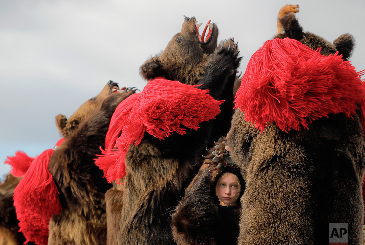 A child wearing a bear fur costume dances along with adults during the annual bear ritual gathering in Comanesti, Romania, Friday, Dec. 30, 2016. In pre-Christian rural traditions, dancers wearing colored costumes or animal furs, toured from house to house in villages singing and dancing to ward off evil. In the present, the tradition has moved to Romania's cities too, where dancers travel to perform the ritual for money. (AP Photo/Vadim Ghirda)