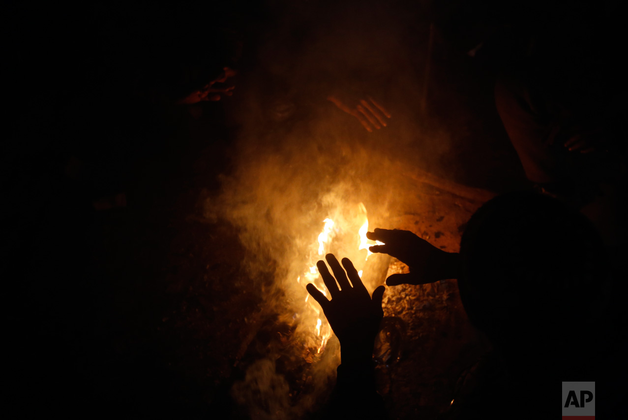 In this Thursday, Jan. 12, 2017 photo, a migrant warms up by a fire inside a crumbling warehouse that has served as a make-shift shelter for hundreds of men trying to reach Western Europe in Belgrade, Serbia. (AP Photo/Darko Vojinovic)