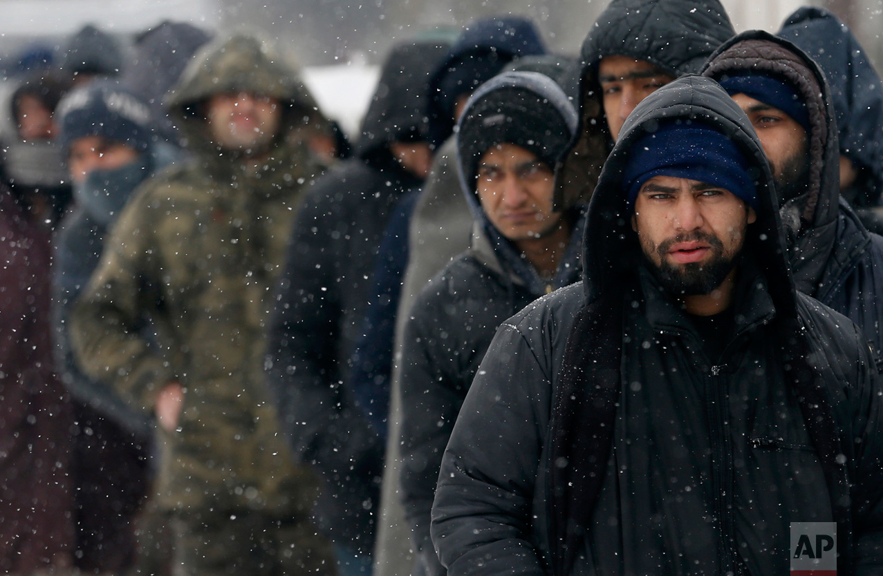 In this Tuesday, Jan. 10, 2017 photo, migrants queue for food in front of an abandoned warehouse in Belgrade, Serbia. (AP Photo/Darko Vojinovic)