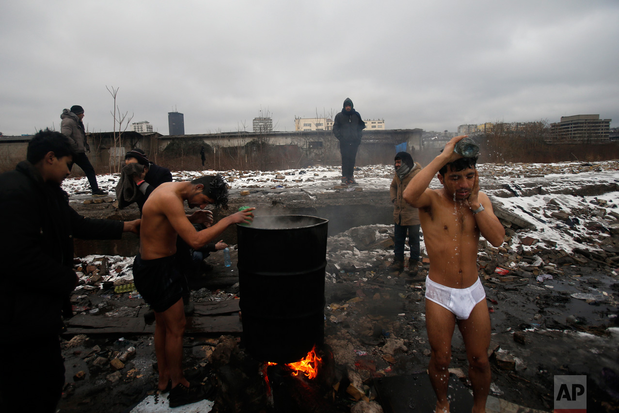 In this Saturday, Jan. 14, 2017 photo, migrants wash themselves outside a crumbling warehouse that has served as a makeshift shelter in Belgrade, Serbia. (AP Photo/Darko Vojinovic)