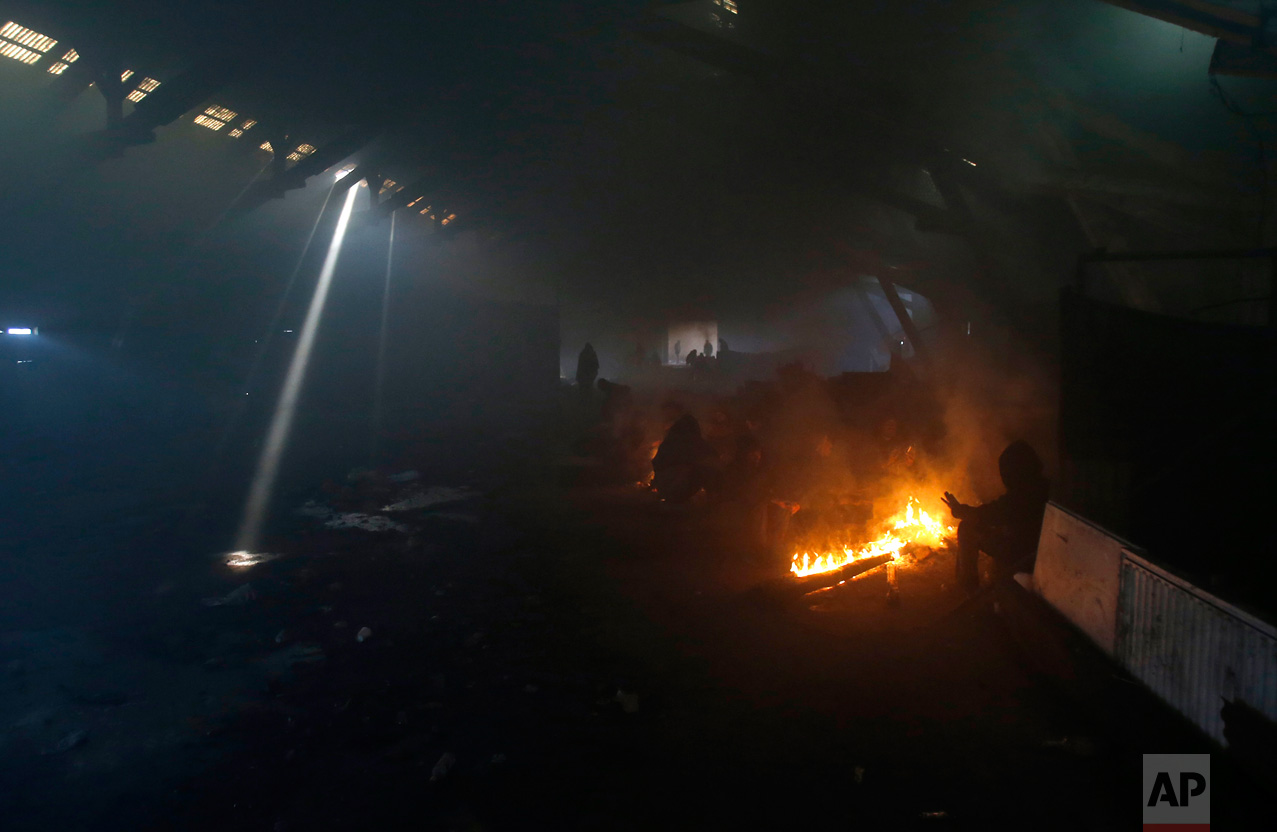 In this Sunday, Jan. 8, 2017 photo, migrants warm themselves by the fire in an abandoned warehouse in Belgrade, Serbia. It was a week in frigid hell for hundreds of migrants squatting in an abandoned warehouse in the Serbian capital of Belgrade while trying to move on toward Western Europe. (AP Photo/Darko Vojinovic)