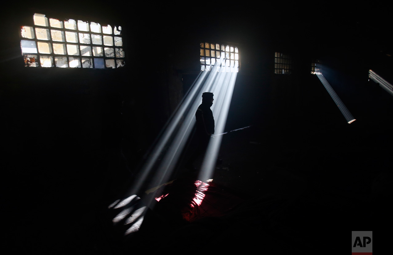 In this Sunday, Jan. 8, 2017 photo, a migrant stands in an abandoned warehouse in Belgrade, Serbia. When the weather suddenly turned nasty it sent temperatures plummeting way below zero and cold wind started to blow pushing into every corner of make-shift migrant shelter. (AP Photo/Darko Vojinovic)