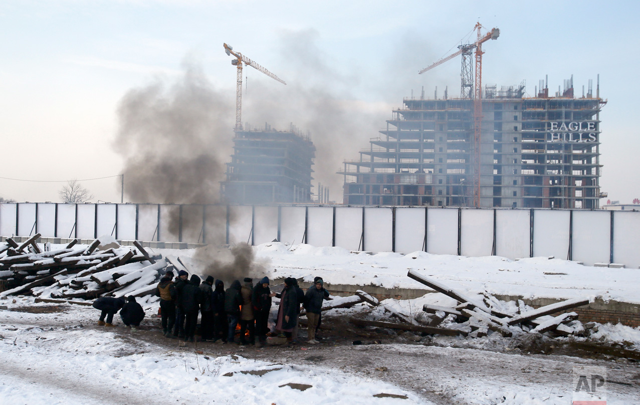 In this Tuesday, Jan. 10, 2017 photo, migrants warms themselves up by a fire next to a crumbling warehouse that has served as a make-shift shelter for hundreds of men trying to reach Western Europe in Belgrade, Serbia. Wrapped in blankets, people huddled next to each other desperately trying to keep warm by the fires they lit inside and outside the building. (AP Photo/Darko Vojinovic)