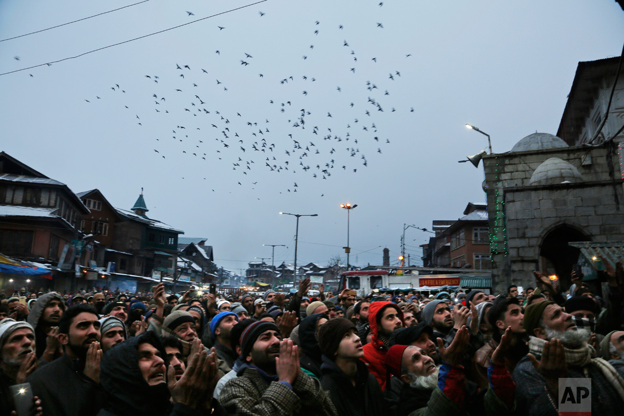 A flock of birds fly past Kashmiri Muslim devotees praying during a display of a relic of Sufi saint Syed Abdul Qadir Jilani at his shrine in Srinagar in Indian-controlled Kashmir, Tuesday, Jan. 10, 2017. Thousands thronged the shrine Tuesday to mark the saint's Urs, an annual commemoration. (AP Photo/Mukhtar Khan)