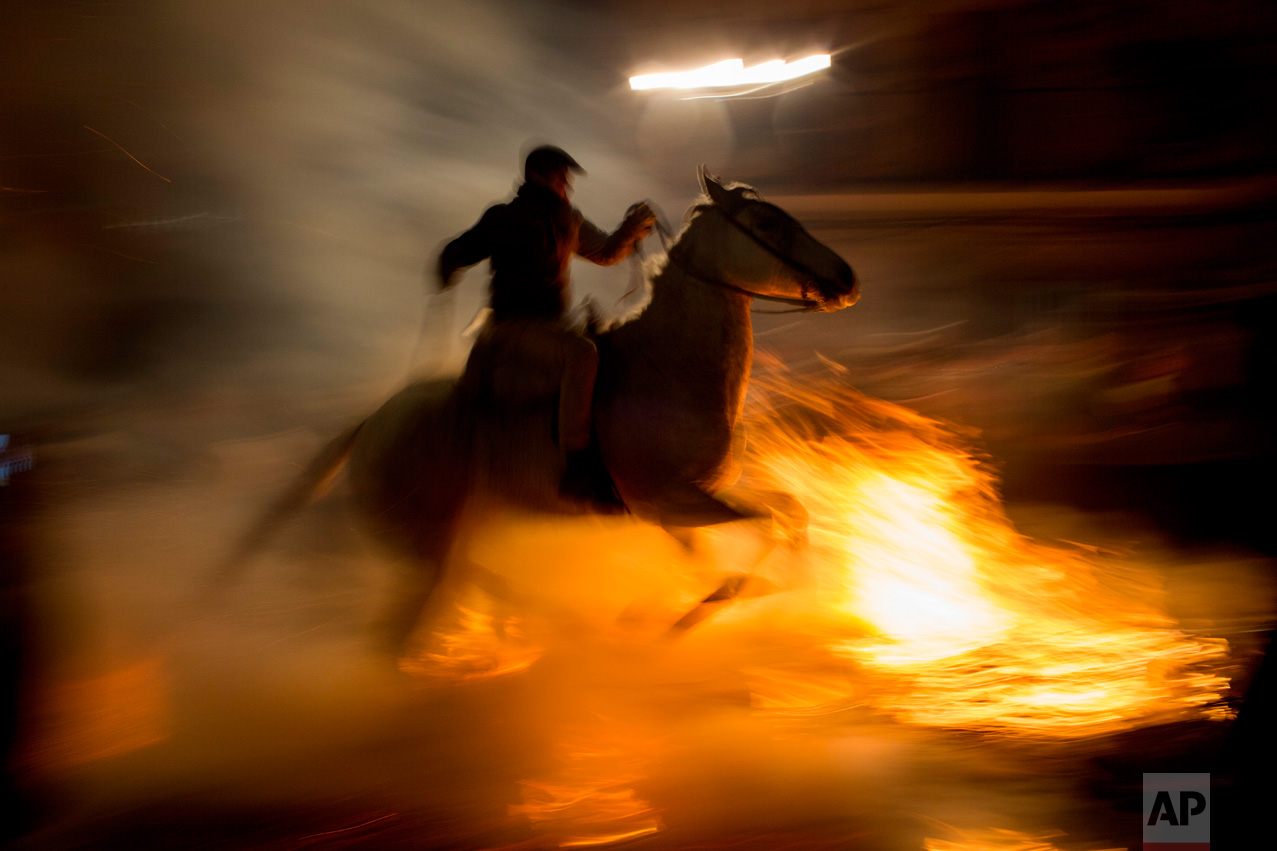 A man rides a horse through a bonfire as part of a ritual in honor of Saint Anthony the Abbot, the patron saint of domestic animals, in San Bartolome de Pinares, about 100 km west of Madrid, Spain, on Monday, Jan. 16, 2017. (AP Photo/Emilio Morenatti)