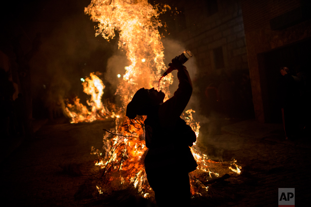 A woman drinks wine man next to a bonfire as part of a ritual in honor of Saint Anthony the Abbot, the patron saint of domestic animals, in San Bartolome de Pinares, about 100 km west of Madrid, Spain on Monday, Jan. 16, 2017. (AP Photo/Emilio Morenatti)