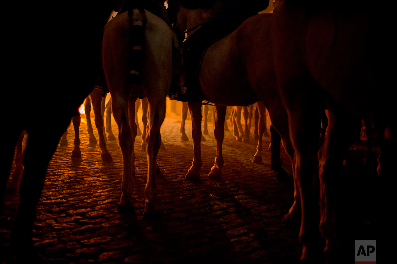 Men ride horses next to a bonfire as part of a ritual in honor of Saint Anthony the Abbot, the patron saint of domestic animals, in San Bartolome de Pinares, about 100 km west of Madrid, Spain on Monday, Jan. 16, 2017. (AP Photo/Emilio Morenatti)