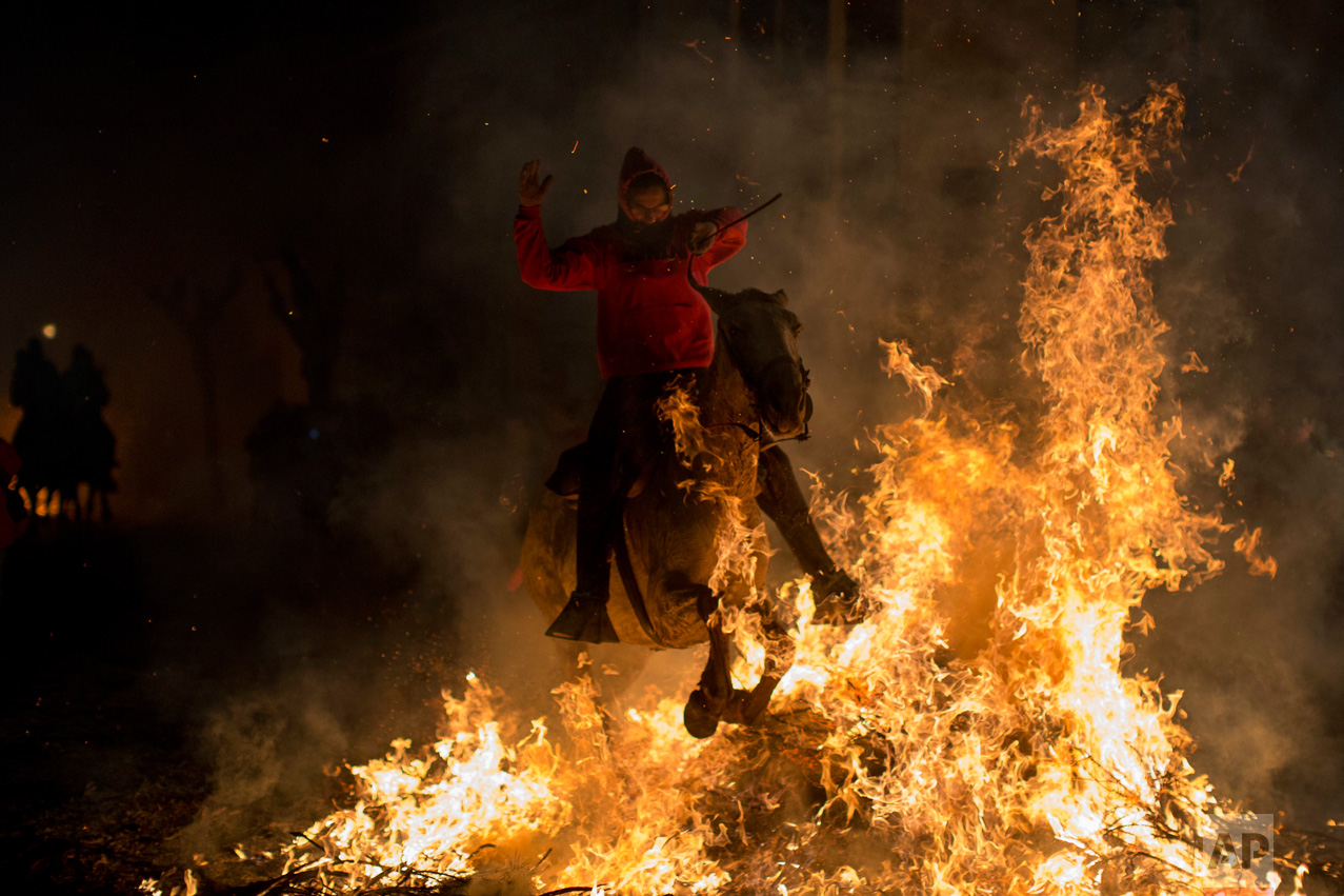 A man rides a horse through a bonfire as part of a ritual in honor of Saint Anthony the Abbot, the patron saint of domestic animals, in San Bartolome de Pinares, about 100 km west of Madrid, Spain on Monday, Jan. 16, 2017. (AP Photo/Emilio Morenatti)