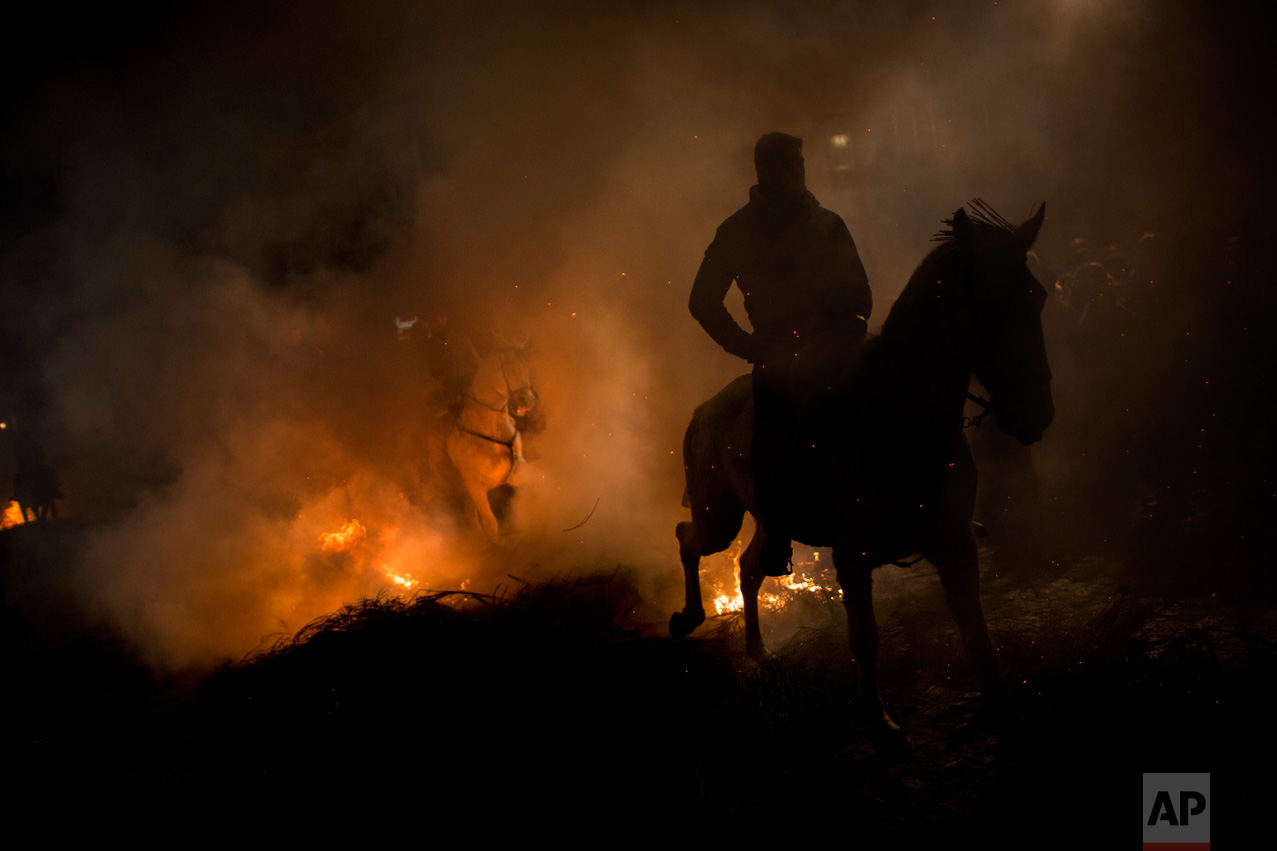 Men ride horses through a bonfire as part of a ritual in honor of Saint Anthony the Abbot, the patron saint of domestic animals, in San Bartolome de Pinares, about 100 km west of Madrid, Spain on Monday, Jan. 16, 2017. (AP Photo/Emilio Morenatti)